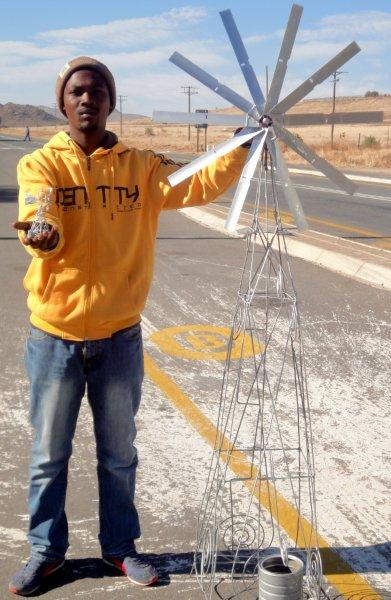 Jonathan Rondganger has been making wire ornaments for three years.  He is showing one of the smallest windmills and standing next to one of the larger ones